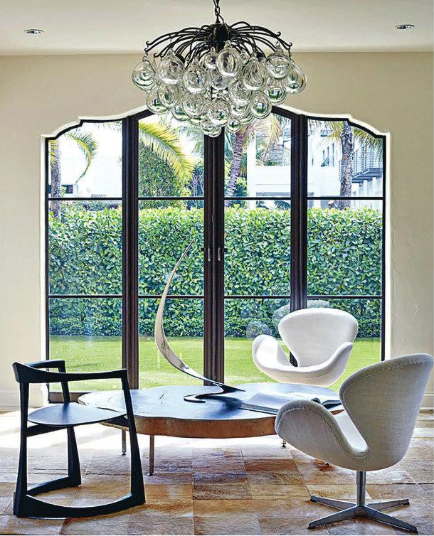 A custom handblown-glass chandelier by Dawkins in a home in Miami Beach; an 18th-century Italian mirror in an apartment in Manhattan